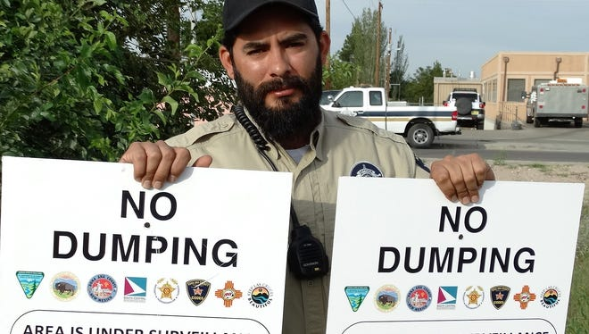 DAC ACO/Codes Enforcement Officer Kevin Apodaca holds signs that are posted after an illegal dump site is cleaned up. The Codes Enforcement crew of three removed more than 27 tons of illegally dumped materials in the desert during six and a half weeks of cleanup this summer.
