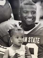 Carlos Marino holds a friend's daughter at the August 1990 Spartan football press day.
