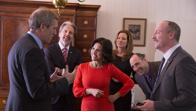 Vice President Tom James (Hugh Laurie), left, charms President Selina Meyer (Julia Louis-Dreyfus), in red, and her staff in HBO's 'Veep.'