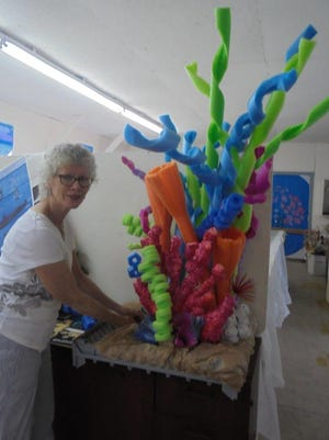 Susan Monroe Kalb fashions a portion of the under-the-sea-themeddecorations for the Crawford County Fair flower show using pool noodles, many of whichwere recycled.