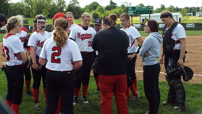 Harrison High School softball coach Sara Loete talks with her team before a game.