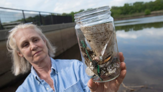 Co-Director of the Center for Urban Environmental Sustainability Beth Ravit holds a jar containing plastic trash picked up at a Raritan River boat ramp