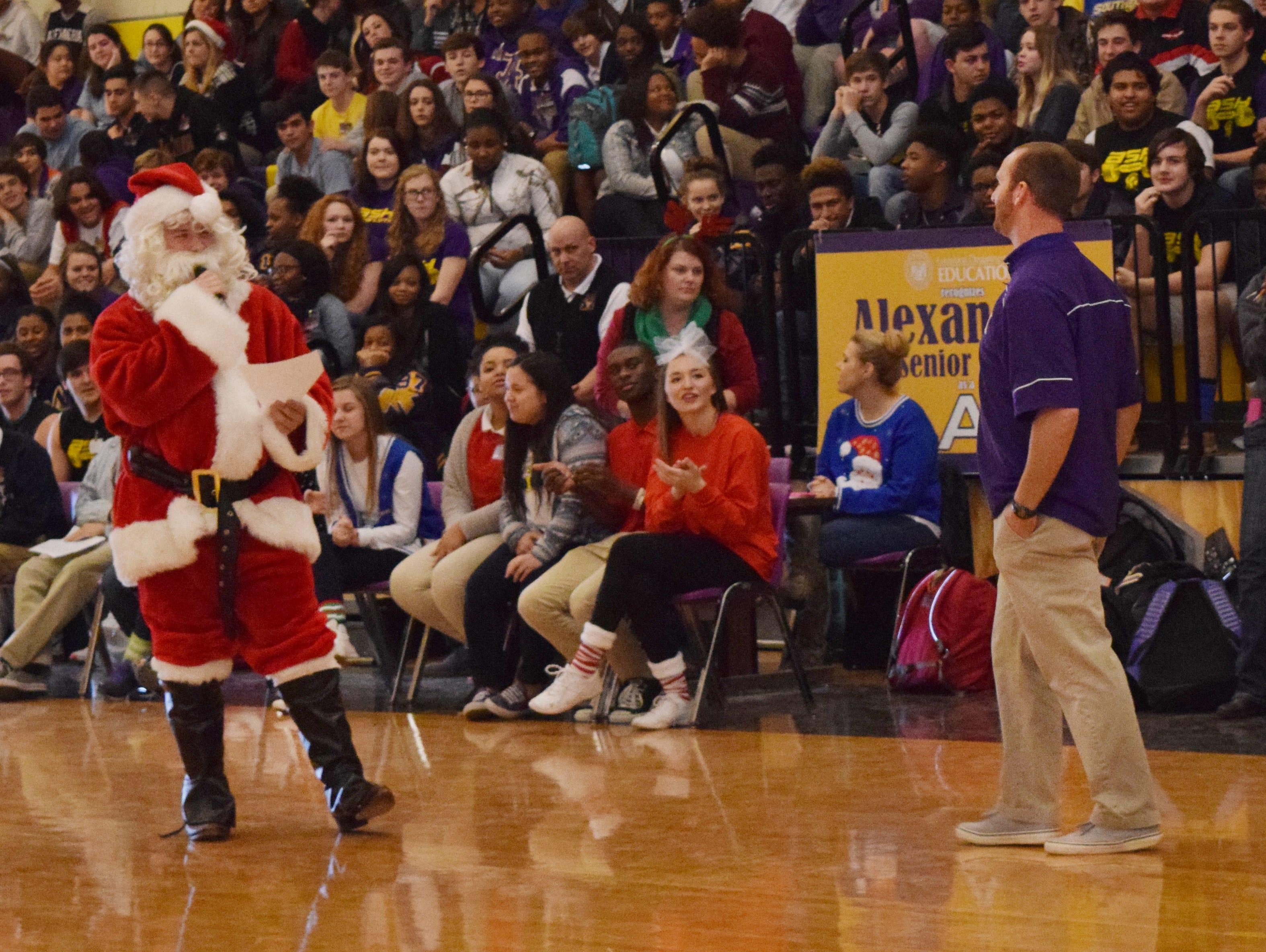 Santa Claus announces to the Alexandria Senior High School student body that Thomas Bachman (right) is the new head football coach.