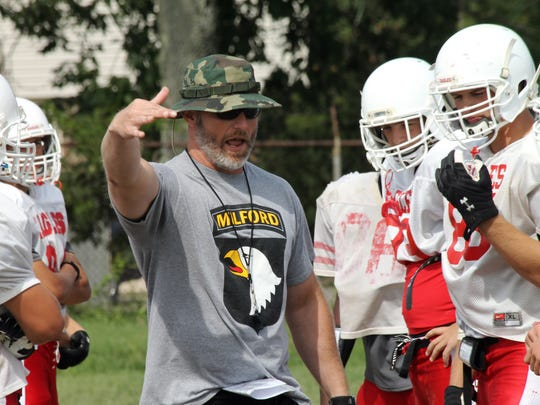 Milford High School head football coach Shane Elkin instructs his players during a practice.