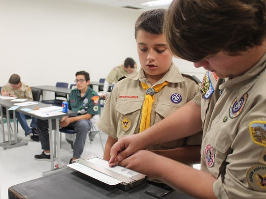 Ryan Wimberley, 12, and Connor Stone, 17, practice fingerprinting while earning a merit badge.