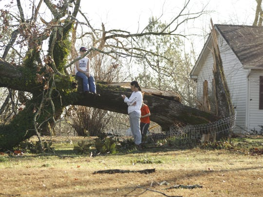 A family waits for help to arrive to begin clearing the damage left in the Canaan community following Wednesday night's deadly tornadoes in Mississippi. The Benton County community was in the path of the storm that is cited for at least four deaths in the county alone.