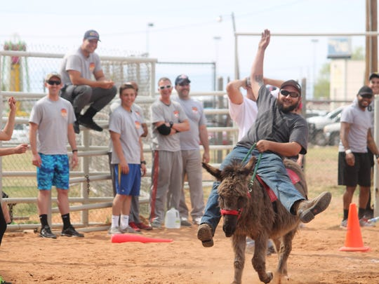 A member of the Otero County Sheriff's Department celebrates making it to the home plate with his donkey.