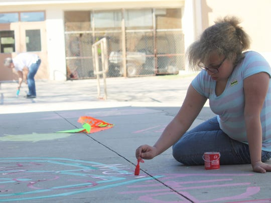 Jennifer Curry, 7th grader at Chaparral Middle School, paints the main walkway with chalk messages against using tobacco.