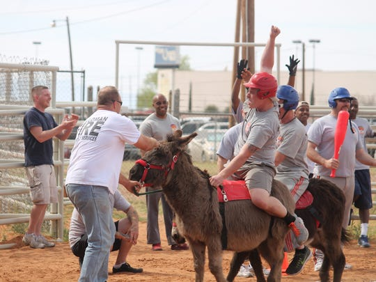 In this file photo, Holloman Air Force Base firefighters celebrate a victory over the Otero County's Sheriff's Office. The two entities will meet again in a donkey baseball rematch on March 17.