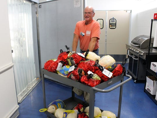 House of Hope volunteer Mike Powers stocks the Stuart Client Choice pantry's freezer with hundreds of pounds of donated hams and turkeys.