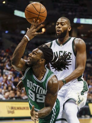 Boston Celtics' Jae Crowder tries to pass the ball back as he is fouled by Milwaukee Bucks' Greg Monroe during the second half of an NBA basketball game Tuesday in Milwaukee.