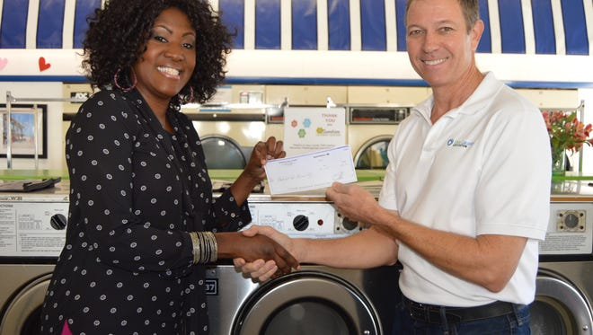 """Eve Kyomya, director of Community Development for Indian River Habitat for Humanity, accepting a check from Sunshine Laundries co-owner Tom Rhodes. Fourth annual """"Washer Blessing"""" at Sunshine Laundries recently donated 25 percent of the gross proceeds to the local Habitats for Humanity."""
