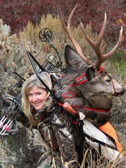 Tiffany Haugen shows a mule deer she harvested bowhunting.