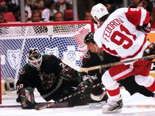 Sergei Fedorov scores on Phoenix Coyote goalie Jimmy Waite and defenseman Gerald Diduck during an April 1998 game, at Joe Louis Arena.