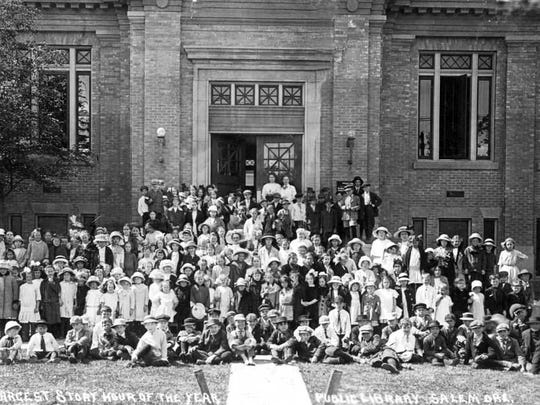 """A group of children attend a """"story hour"""" event at the Salem Public Library, circa 1913. Salem Public Library Historic Photograph Collections, Salem Public Library"""