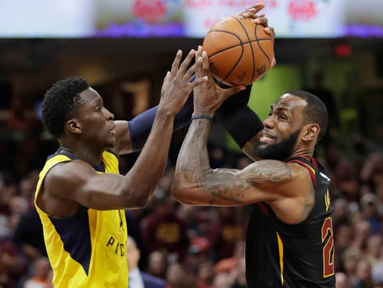 Cleveland Cavaliers' LeBron James, right, drives past