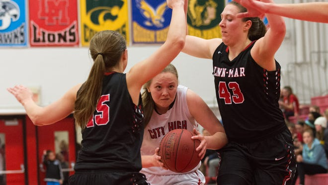 Iowa City Highs Courtney Joens drives against Linn-Mar's Alie Akers (left) and Amanda Ollinger during the second half of the Little Hawks loss to the Lions at City High School in Iowa City. Friday, Feburary 5, 2016.
