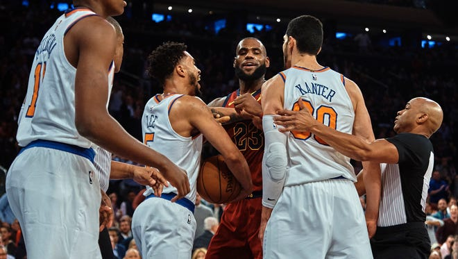 Cleveland Cavaliers' LeBron James, center, discusses with New York Knicks' Enes Kanter, center right, and Courtney Lee, center left, during the first half of a NBA basketball game at Madison Square Garden in New York, Monday, Nov. 13, 2017.