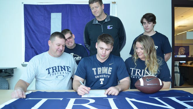 Lakeview's Steven Laws will play college football at Trine University as he made his commitment official on National Signing Day. He is joined by his parents Susan and David Laws, his brothers, Blake and Anthony and Lakeview coach Matt Miller.