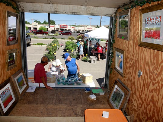Doug Miller, left, of Thunder Visions, sells his art at the Farmington Growers Market on Saturday at the Farmington Museum at Gateway Park.