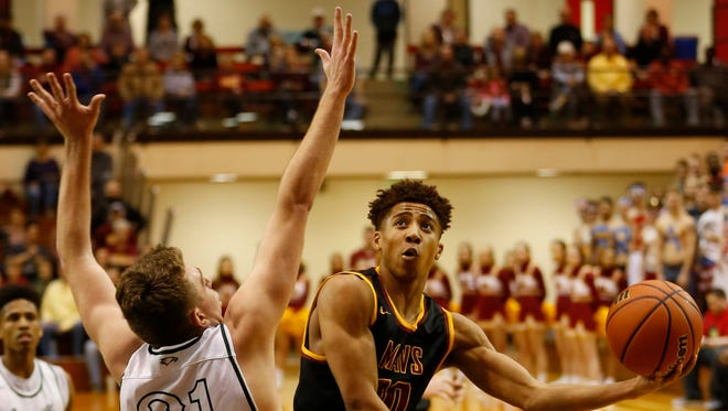 Robert Phinisee of McCutcheon loops a shot over Will Alcock of Zionsville in the sectional championship Saturday, March 3, 2018, at Lafayette Jeff. Zionsville defeated McCutcheon 60-50.