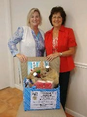 The GFWC Treasure Coast Women have completed their November Fall Harvest Food Drive. Several local businesses allowed the club to place donation boxes in their offices and about 350 non-perishable food items were collected and divided between the Hope Family Homeless Center and Our Father's Table. The Home Life Department of the club also supplied a complete Thanksgiving dinner to a local veterans family.  Daisy Burns, left, employee of Sea Turtle Real Estate, gives their box of donated food to Treasure Coast Women's Chairman Kathy Merritt.