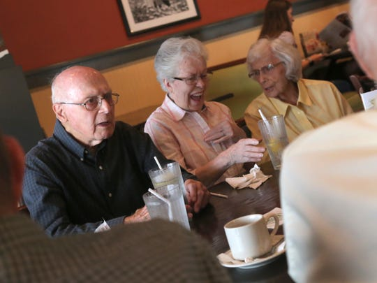 Mary-Alice Loesh, right, talks with Anna-Ruth Wiehm and her husband Helmut, left, during the monthly meeting of the Mansfield Senior class of the 1946 at O'Charley's in Ontario.