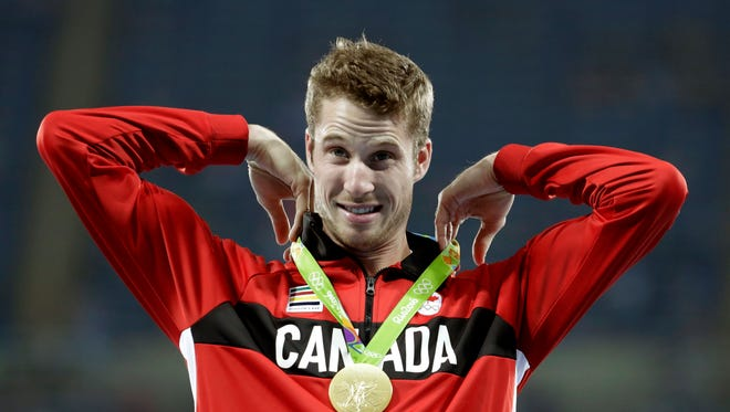 Gold medal winner Canada's Derek Drouin stands on the podium after the award ceremony for the men's high jump during the athletics competitions of the 2016 Summer Olympics at the Olympic stadium in Rio de Janeiro, Brazil, Wednesday, Aug. 17, 2016. (AP Photo/Charlie Riedel)