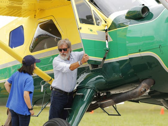 FILE - In this July 28, 2016, file photo, Harrison Ford opens the door on his plane for Jodie Gawthorp, of Westchester, Ill., who was selected to fly with Ford, at the Experimental Aircraft Associations AirVenture air show at Wittman Regional Airport in Oshkosh, Wis. Ford told an air traffic controller he was distracted and concerned about turbulence from another aircraft when he mistakenly landed his small plane on a taxiway at a Southern California airport in Feb. 2017.