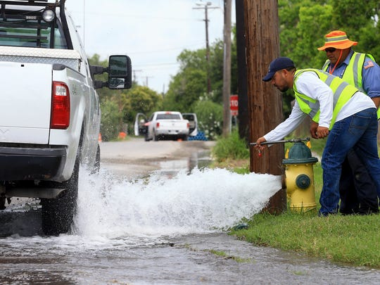 Crew members from the utilities department flush water out from a hydrant May 14 on the corner of Glenmore Street and Kentner Street in Corpus Christi.