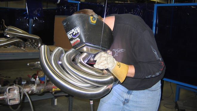 A welder puts the finishing touches on a Custom Marine exhaust system in this 2006 file photo.