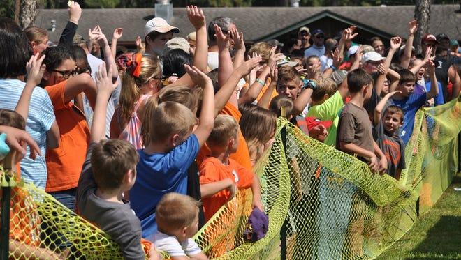 A group of kids  gather around as door prizes are given out at Central Louisiana' s National Hunting and Fishing Day event held Saturday in Woodworth.