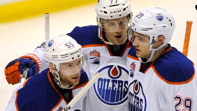 Edmonton Oilers' Oscar Klefbom (77), of Sweden, and Leon Draisaitl (29) congratulate Mark Letestu (55) after his goal against the St. Louis Blues during the second period of an NHL hockey game, Tuesday, Feb. 28, 2017, in St. Louis. (AP Photo/Bill Boyce)