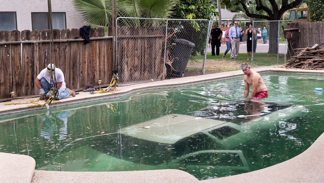 Derek Shores, right, and crew from Jameson Hydro Crane Service prepare to lift a soggy 1999 Chevy Silverado from a Visalia's backyard pool on Thursday, August 3, 2017. Almost exactly a day earlier a female driver, still sought by police, crashed the truck through the fence, narrowly missing other cars and the house next door. No injuries were reported.