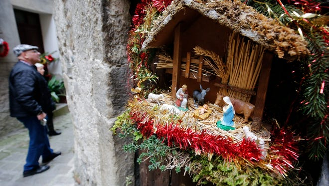 People pass by a nativity scene during the 18th Nativity Scenes exhibition in the street of Luceram in southeastern France. EPA/SEBASTIEN NOGIER