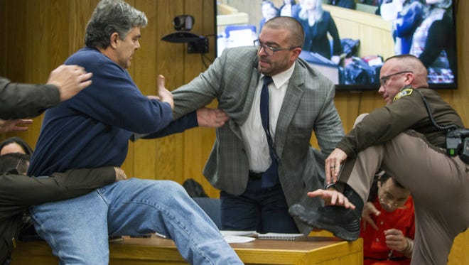 Randall Margraves, father of three daughters abused by of Larry Nassar , left, lunges at Nassar, bottom right, Friday, Feb. 2, in Eaton County Circuit Court in Charlotte, Mich.