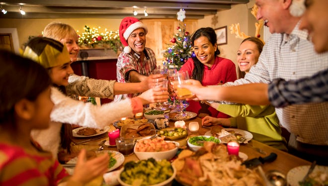 A family toast and celebrate at Christmas dinner.