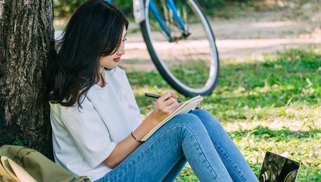 Woman with pen writing on a notebook sitting on grass in park