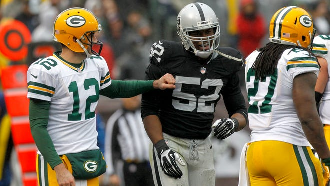 Dec 20, 2015; Oakland, CA, USA; Green Bay Packers quarterback Aaron Rodgers (12) talks with Oakland Raiders outside linebacker Khalil Mack (52) during a break in the action in the second quarter at O.co Coliseum. Mandatory Credit: Cary Edmondson-USA TODAY Sports