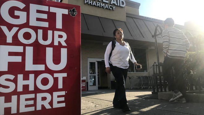 File photo taken in Jan. 2018 shows passersby near a Rite Aid pharmacy and its flu advertisement sign in Oakland, Cal.