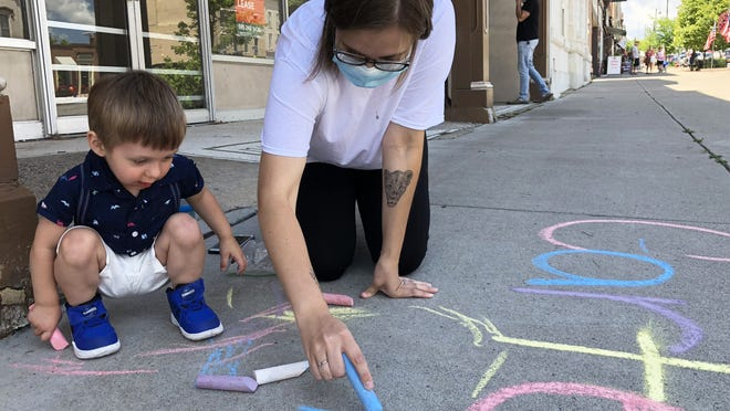Ally Castro gives Carter Bellis-Williams a hand in writing his name in chalk on a downtown Canandaigua sidewalk on Friday as part of Arts in Canandaigua.