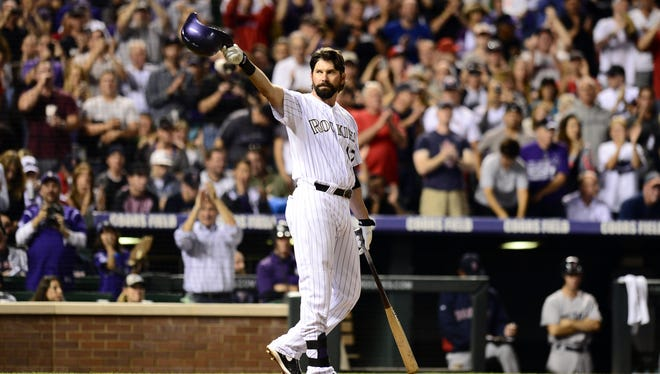 The Rockies' Todd Helton tips his helmet in his first at-bat Wednesday in his last career home game, then hit a home run in that at-bat.