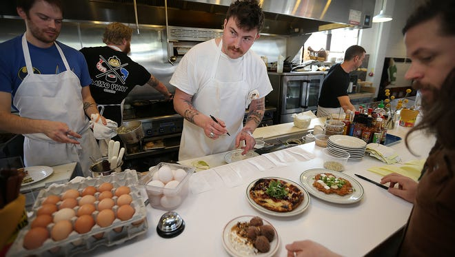 Milktooth owner Jonathan Brooks keeps ahead of the many brunch orders Saturday morning.