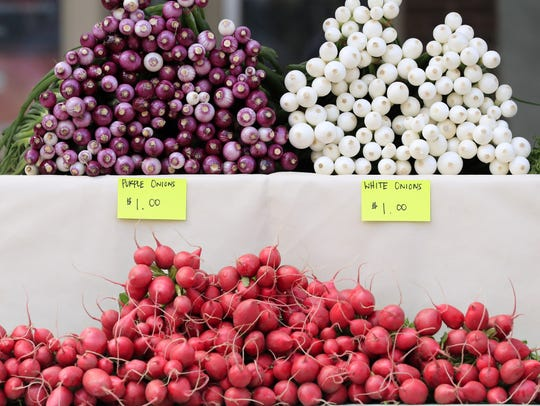 Fresh onions and radishes are displayed Wednesday at