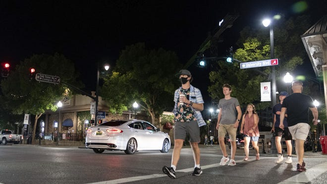 Students wander among heavy car traffic on The Strip, the University of Alabama's bar scene Saturday, Aug. 15, 2020, in Tuscaloosa, Ala. More than 20,000 students returned to campus for the first time since spring break with numerous school and city codes in effect to limit the spread of Covid-19.