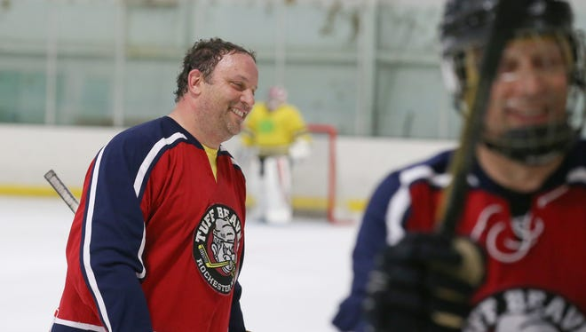 Ed Giggie is all smiles as he jokes with teammates at the bench between the first and second periods during their men's league hockey game at the Rochester Ice Center in Fairport Monday, Sept. 18, 2017.
