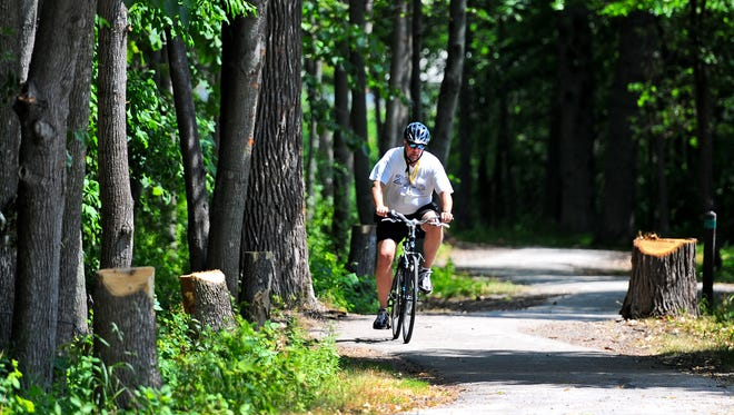 A cyclist rides on the East River Trail in Green Bay.