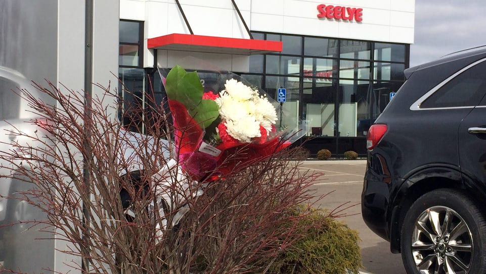 Flowers are place in front of a car dealership, the