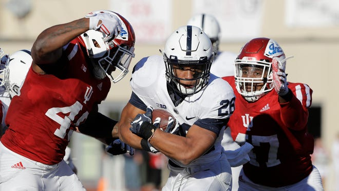 Penn State's Saquon Barkley is tackled by Indiana's Marcelino Ball, left, and Robert McCray III during the second half of an NCAA college football game Saturday, Nov. 12, 2016, in Bloomington, Ind. Penn State defeated Indiana 45-31.