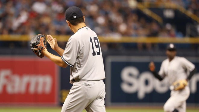 New York Yankees starting pitcher Masahiro Tanaka (19) claps to shortstop Didi Gregorius (18) as he makes a double play to end the sixth inning against the Tampa Bay Rays at Tropicana Field.